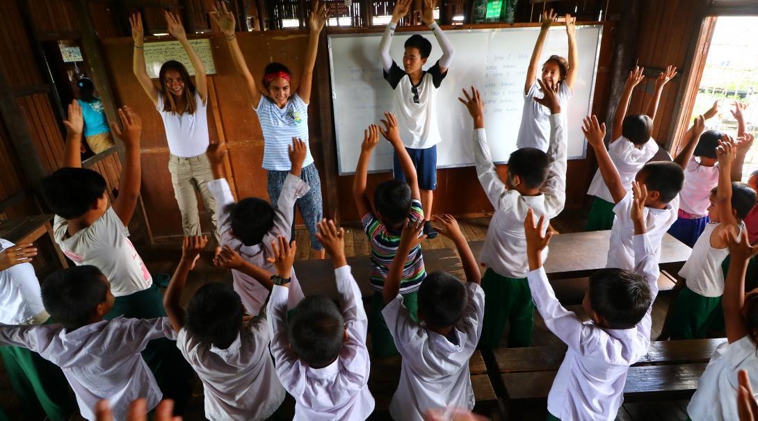 Voluntaria y estudiantes en una clase divertida mientras les enseña inglés.